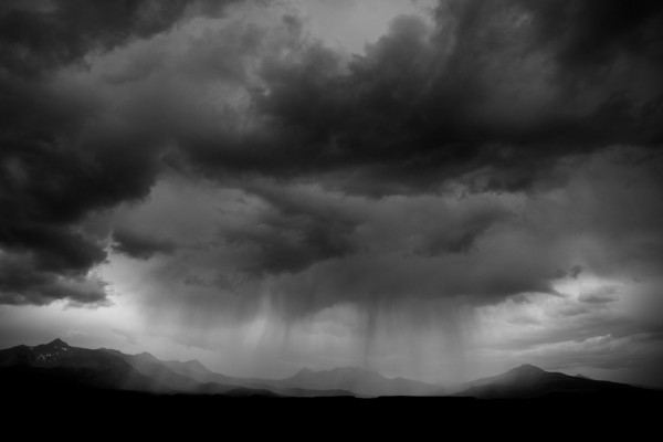 A cloudburst drops virga across the mountain landscape.